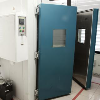 View of the environmental test chamber, a square enclosure with two thick half-open doors and a control panel with buttons, inside the laboratory