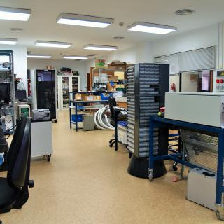 General view of the electronic design laboratory with several workbenches, electronic racks and cabinets for components and electronic parts