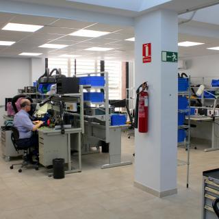 General view of the Electronics Workshop with several workbenches, cabinets and boxes to store components and electronic parts, and a technician working in one of the workbenches