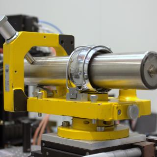 View of the alignment telescope in the laboratory. Small cylindrical telescope on an adjustable metal base